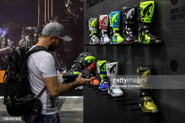 A man looks at motorcycles boots at the stand of Italian manufacturer Forma during the 76th edition of EICMA on November 7 2018 in Milan Italy EICMA...