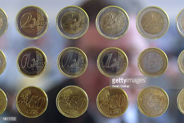 A man looks at new Euro coins suspended in glass during a Euro presentation by the European Central Bank August 30 2001 in Frankfurt Germany In two...