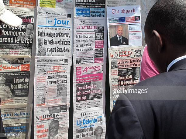 Man looks at newspapers bearing headlines on ousted Central African Republic president Francois Bozize, on March 26, 2013 in Yaounde. Bozize, who...