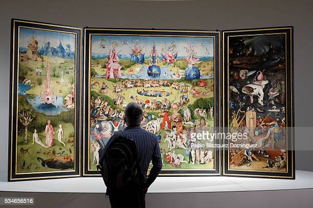 A man looks at of 'The Garden of Earthly Delights Triptych' by the Dutch painter Hieronymus Bosch during a press preview of the 'El Bosco' 5th...