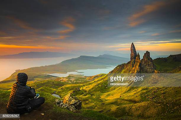 Man looks at old man of storr at sunrise