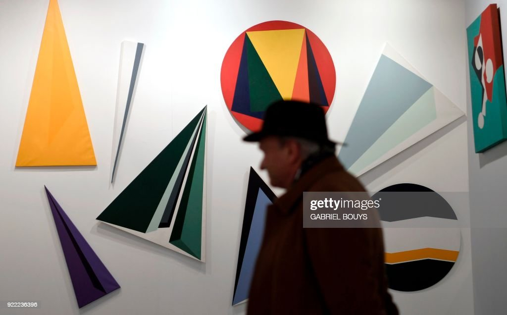 A man looks at paintings by Brazilian artist Irene Buarque during the ARCO International Contemporary Art Fair opening in Madrid on February 21, 2018. Madrid hosts the annual Arco contemporary art fair, one of Europe's biggest, from February 21 to February 25, 2018. /