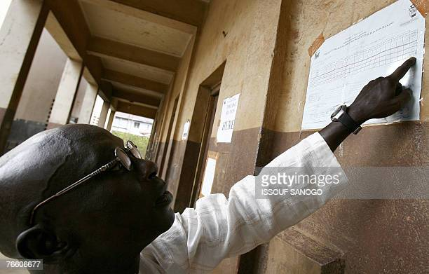 A man looks at partial results of presidential elections 09 September 2007 at a voting bureau in Freetown a day after the second round of elections...