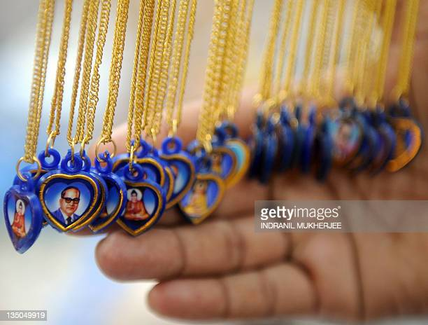 A man looks at pendants with images of Bhimrao Ambedkar and Lord Gautam Buddha for sale on Ambedkar's 55th death anniversary near the historic...