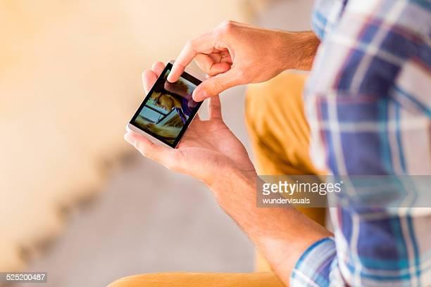 Man sieht in Foto von Freundinnen auf dem Smartphone