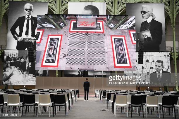 "Man looks at photographs picturing late German fashion designer Karl Lagerfeld, at the start of the ""Karl For Ever"" event to honour him at the Grand..."