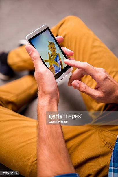 Man Looks At Photos Of Family On Smartphone
