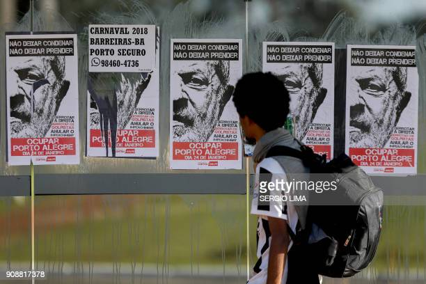 A man looks at pictures of posters placed at a bus stop in Brasilia on January 22 2018 in support of Brazilian former President Luiz Inacio Lula de...