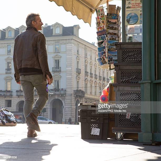 man looks at postcard rack in piazza, city centre - un solo hombre fotografías e imágenes de stock