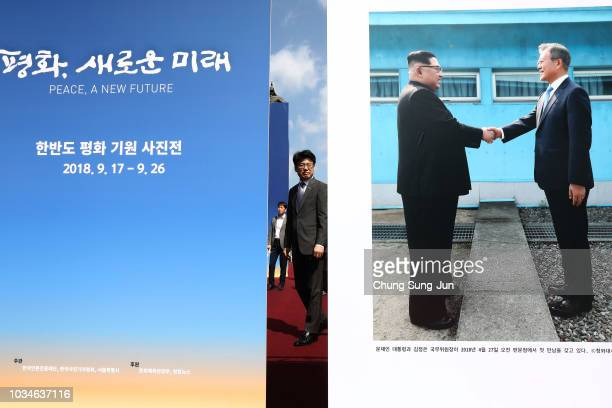 A man looks at posters advertising the summit between South Korean President Moon Jaein and North Korean leader Kim Jong Un during a photo exhibition...