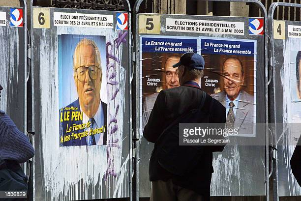 A man looks at posters for French presidential candidates April 21 2002 in Paris Far right National Front party leader JeanMarie Le Pen placed second...