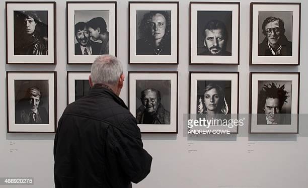 A man looks at protrait photographs of British musician Mick Jagger British theatre director Jonathan Miller British actor Michael Caine British...
