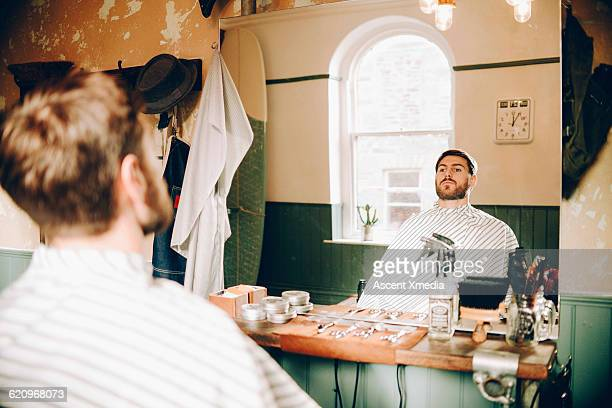 Man looks at reflection in barber shop, after cut