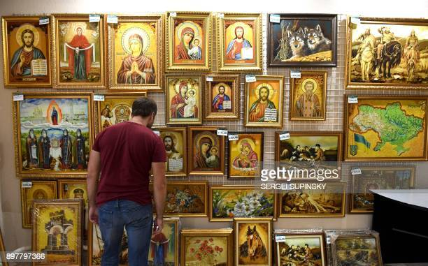 A man looks at religious icons made with amber in an amber shop in Rivne northwestern Ukraine on September 21 2017 Volodymyr Korkosh steps on the...