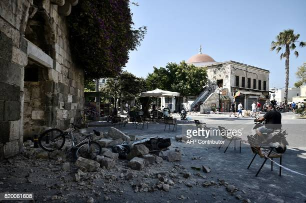 TOPSHOT A man looks at rubble fallen from a quake damaged building on the Greek Island of Kos on July 21 2017 following a 65 magnitude earthquake...
