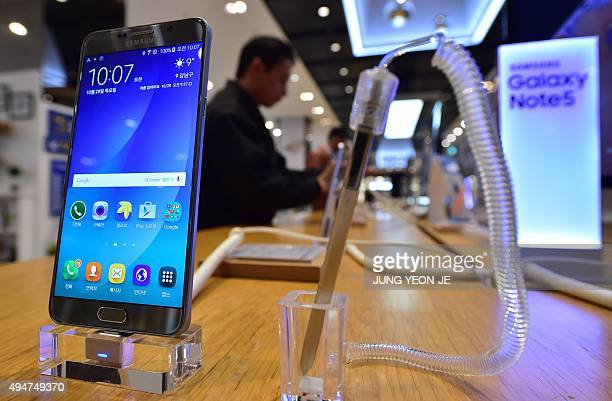 A man looks at Samsung Electronics' Galaxy Note5 at its showroom in Seoul on October 29 2015 South Korea's Samsung Electronics pulled out of an...