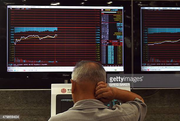 A man looks at screens showing stock market movements at a securities company in Beijing on July 8 2015 China stocks took another plunge on July 8 as...