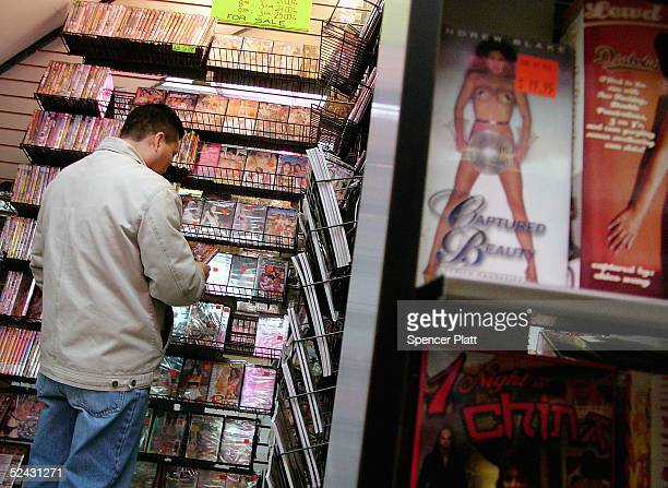 Man looks at sexually explicit DVD's inside an adult store in Times Square March 15, 2005 in New York City. Sex-related shops have started to make a...