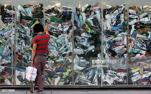 Man looks at sneakers in the window of the Adidas flagship store on August 12, 2008 in Beijing, China.
