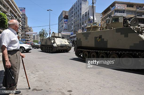 A man looks at tanks of Lebanese Army Forces patrolling on June 6 2013 in a street of the eastern Lebanese city of Tripoli The wave of bloody...