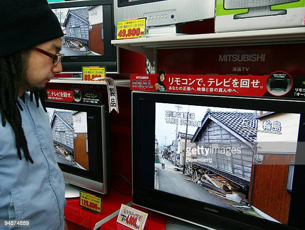 A man looks at televisions showing news of the earthquake at an electronics shop in Tokyo Japan on Sunday March 25 2007 An earthquake of magnitude 67...