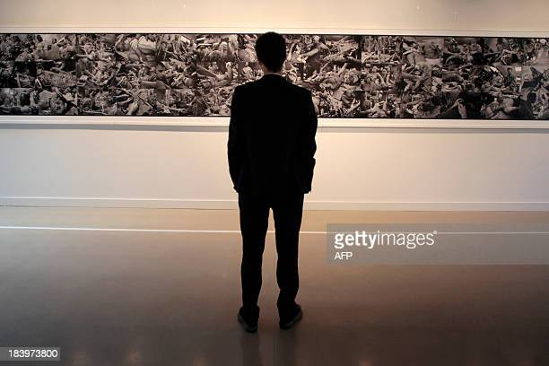 Man looks at the 9,50meters frame composed of sixty James Nachtwey's picture taken in Bagdad in 2003, on October 10, 2013 in Bayeux, western France,...