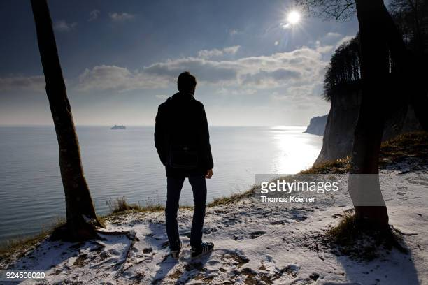 A man looks at the Baltic Sea Kieler Ufer in winter in the Jasmund National Park on the island of Ruegen on February 07 2018 in Glowe Germany