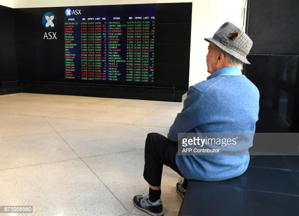 A man looks at the boards at the Australian Securities Exchamge in Sydney on November 7 2017 The benchmark SP/ASX 200 briefly passed 6000 in trading...