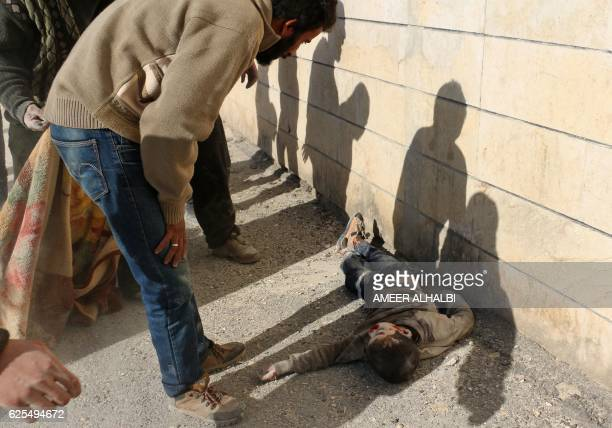 A man looks at the body of a boy following a reported barrel bomb attack on the Bab alNairab neighbourhood of the northern Syrian city of Aleppo on...