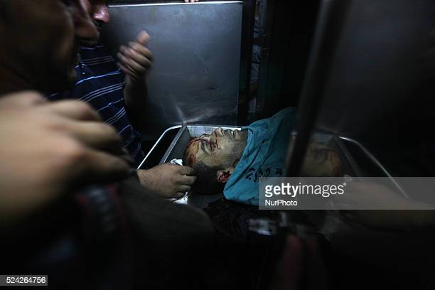 A man looks at the body of a Palestinian militant who medics said was killed in an Israeli air strike at a hospital morgue in Gaza City July 12 2014...