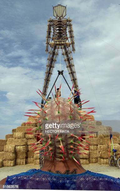 A man looks at the Burning Man effigy as it is prepared for the Burning Man Festival at Black Rock City in Nevada 29 August 2000 An estimated thirty...