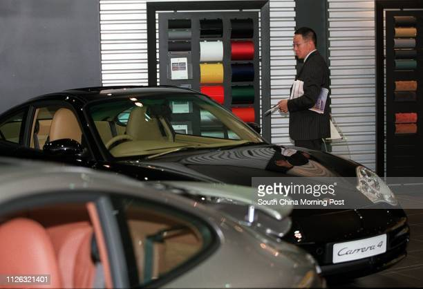 A man looks at the Carrera 4 in a Porsche cars showroom in Causeway Bay