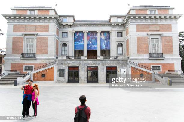 A man looks at the closed Prado Museum while a couple takes a selfie on March 12 2020 in Madrid Spain Many museums have been closed due to an...
