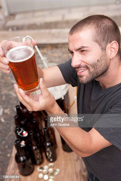 Man looks at the color of his homebrew.