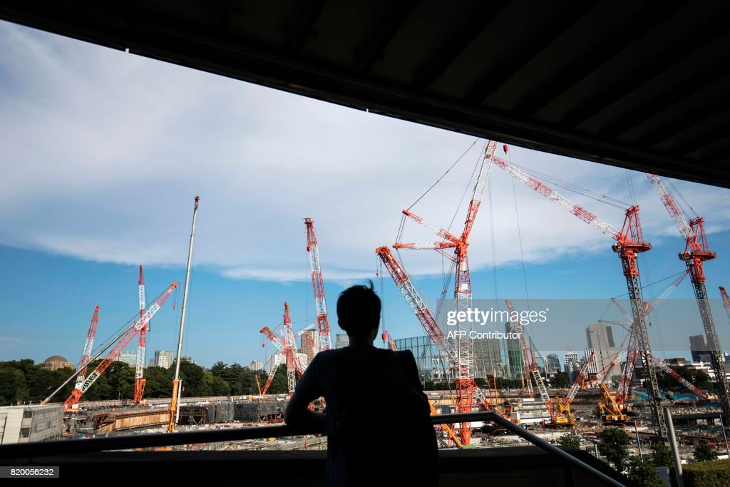 A man looks at the construction site for the National Stadium, venue for the upcoming Tokyo 2020 Olympic Games, in Tokyo on July 21, 2017. The suicide of a 23-year-old worker on Tokyo's Olympic stadium was due to overwork, his family said on July 21, as Japan races to finish building venues for the 2020 Games. / AFP PHOTO / Behrouz MEHRI