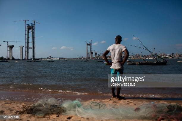 A man looks at the construction site of the MaputoCatembe Bridge which will be the longest suspension bridge in Africa once completed in Maputo on...