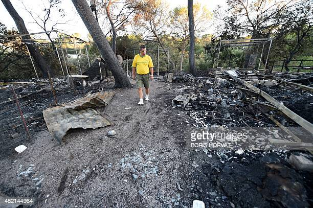 A man looks at the damage at a campsite following a wildfire in BagnolsenForet in the Var department in southern France on July 27 2015 Three...