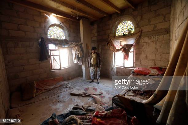 TOPSHOT A man looks at the damage in a building located near the site of an air strike in the Yemeni capital of Sanaa on November 11 2017 The...