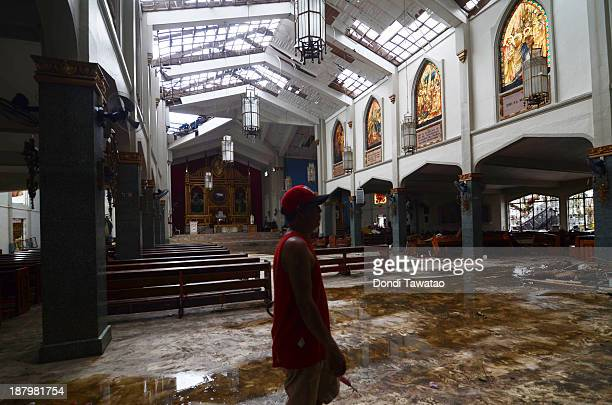 A man looks at the damage inside a church in Tacloban City on November 14 2013 in Tacloban Philippines Typhoon Haiyan which ripped through...