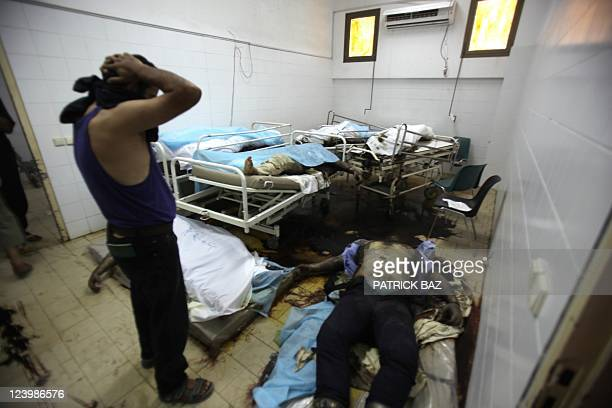 CONTENT A man looks at the dead bodies in the morgue at the general hospital in the restive Abu Salim neighborhood of Tripoli on August 26 2011 The...