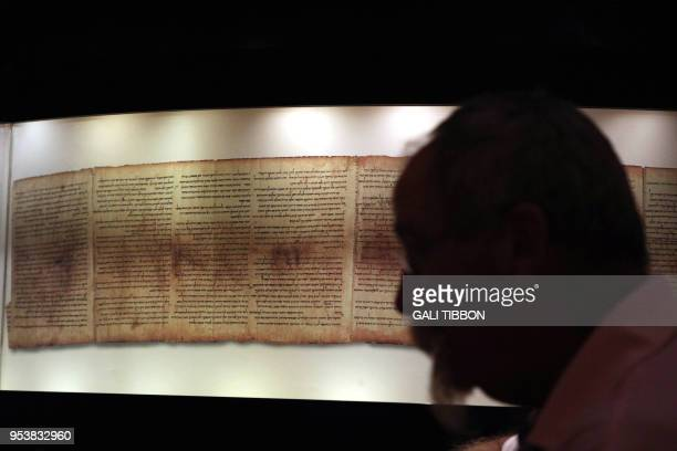 A man looks at the Dead Sea Scrolls found in Qumran caves in the Judean Desert and dated around 120 BCE during a visit to the Shrine of the Book at...