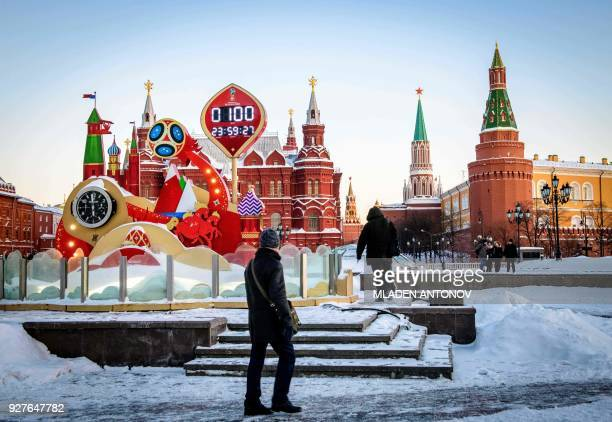 A man looks at the digital FIFA World Cup 2018 countdown clock placed in front of the Red Square and the Kremlin in Moscow marking 100 days to the...