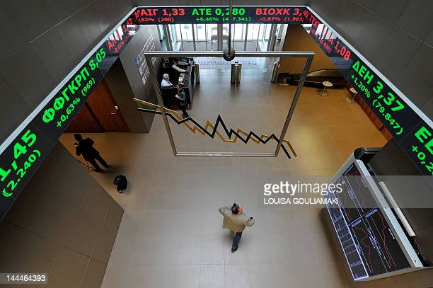 A man looks at the electronic index display at the Athens stock exchange on March 9 2012 Greece on Friday said it was 70 billion euros short of a...