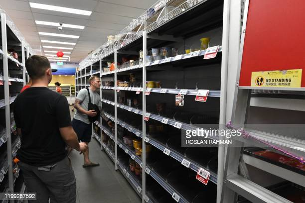 A man looks at the empty shelves what have leftover at a local supermarket in Singapore after panic buying swept through the city after the...