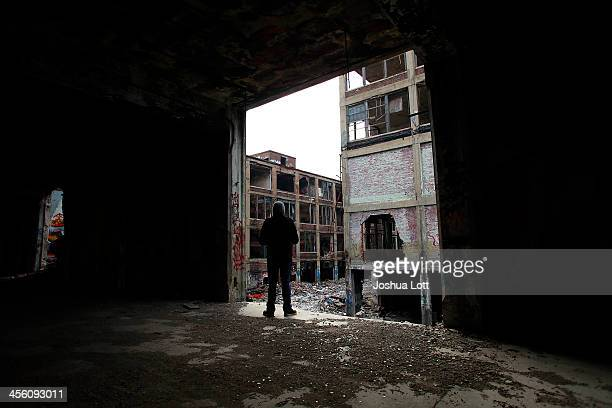 A man looks at the exterior of the abandoned Packard Automotive Plant December 13 2013 in Detroit Michigan Perubased developer Fernando Palazuelo...