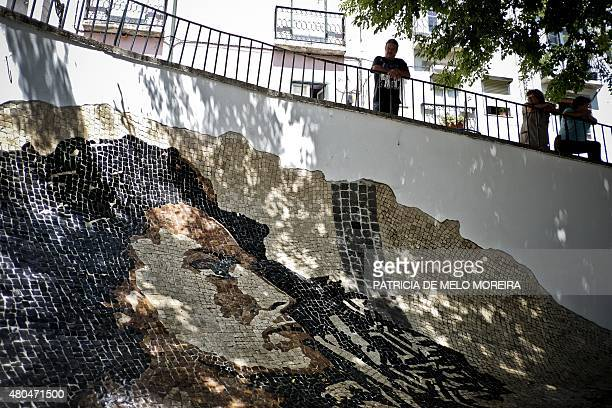 A man looks at the face of Portuguese Fado singer Amalia Rodrigues represented with typical Portuguese cobblestones by the street artist Alexandre...