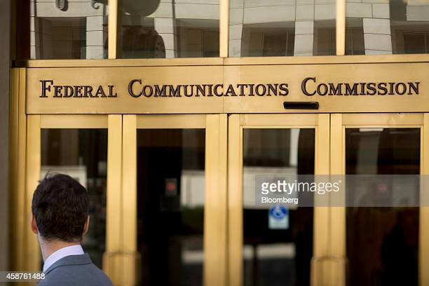 A man looks at the Federal Communications Commission headquarters in this photo taken with a tiltshift lens in Washington DC US on Monday Nov 10 2014...