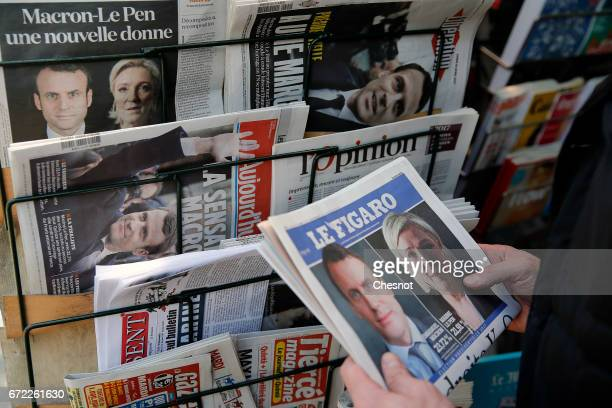 A man looks at the front page of the French newspaper 'Le Figaro' with pictures of French Presidential election candidates Emmanuel Macron and Marine...