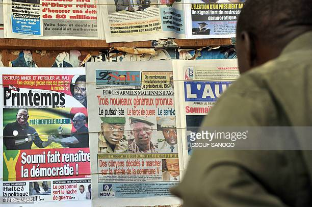 A man looks at the front pages of newspapers on August 15 2013 in Bamako showing the leaders of the coup including Captain Amadou Sanogo that ousted...