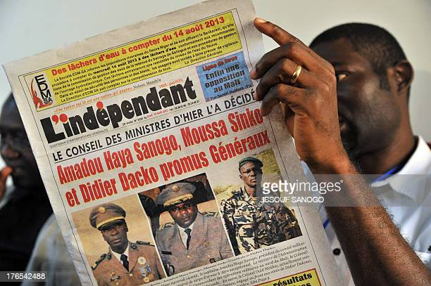 A man looks at the front pages of newspapers on August 15 2013 in Bamako showing the leaders of the coup Amadou Sanogo Moussa Sinko Coulibaly and...